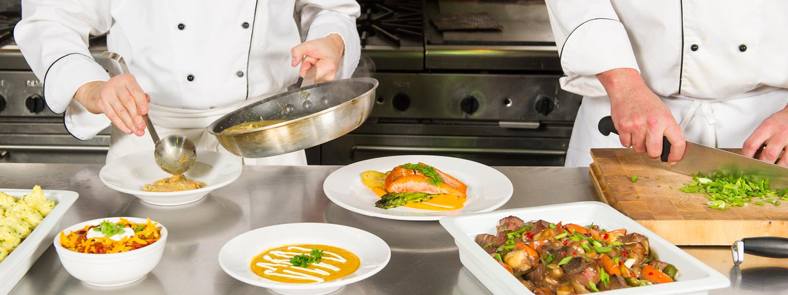 Chefs plating dishes in restaurant web